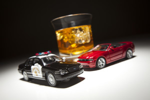 Police and Sports Car Next to Alcoholic Drink Under Spot Light.